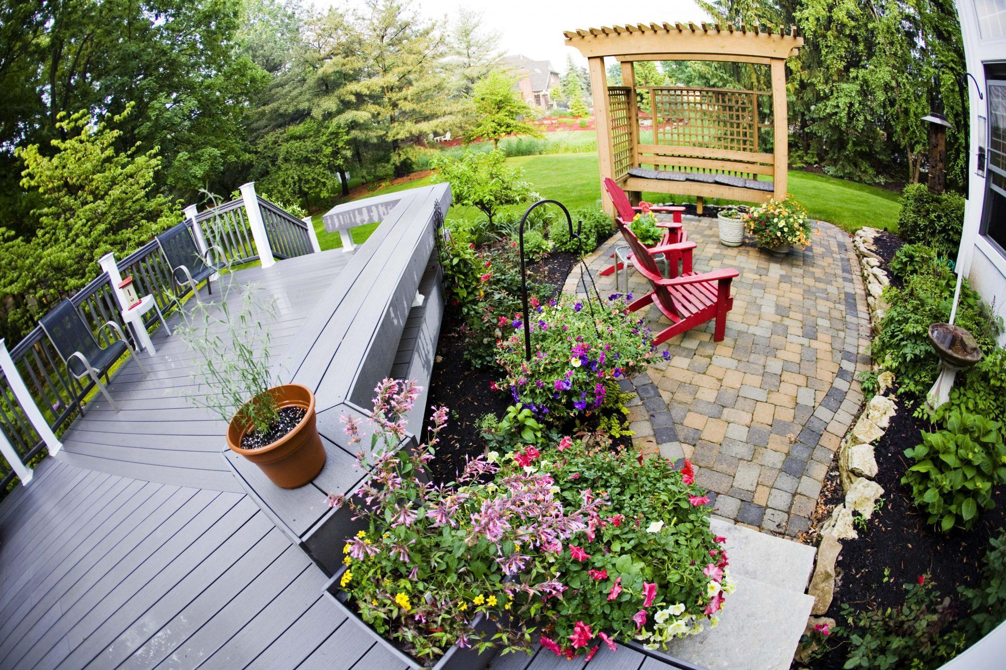 The perfect garden featuring beautiful planted flowers, wooden seat and an arbour